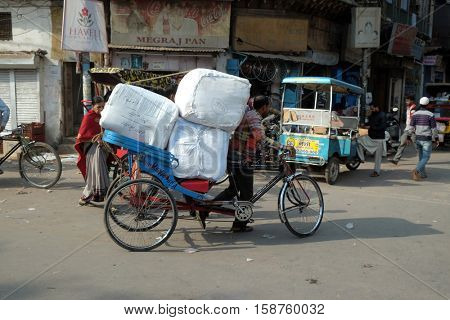 DELHI, INDIA - FEBRUARY 13 : Hard working indians pushing heavy load through streets of Delhi, India on February 13, 2016. Human labor is still cheaper than motorized vehicles.