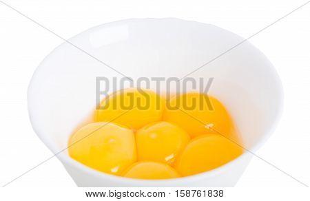 Fresh egg yolks on white bowl closeup. Macro. Isolated on a white background.