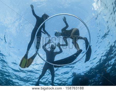 Underwater shot of the people snorkeling in the tropical sea and bubble ring ascending from the depth