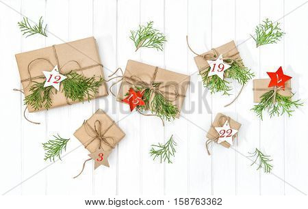 Wrapped gifts Advent calendar with christmas tree branches decoration on bright wooden background. Flat lay
