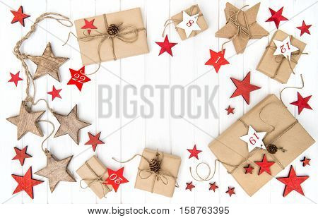 Wrapped gifts Advent calendar Christmas decoration red stars on bright wooden background. Flat lay