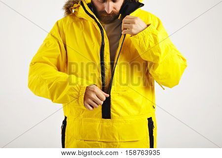 Serious bearded young man zipping up his bright yellow warm snowboarding anorak isolated on white