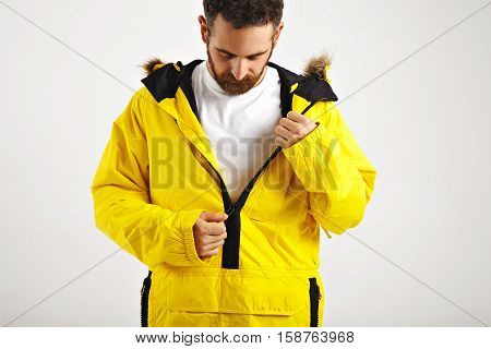 Young bearded snowboarder zipping up his yellow parka over plain white cotton t-shirt isolated on white