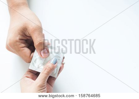 Condom in male hand and female hand give condom safe sex concept on white background