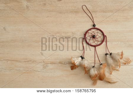 A dream catcher isolated on a wooden background