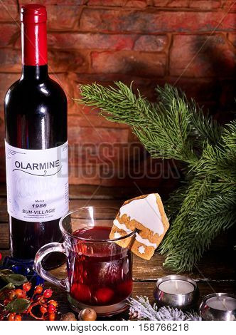 Bottle of red wine and mug with hot mulled wine. How prepared homemade mulled wine. Winter hot drink. Gingerbread cookie in form of house is decorated mug with hot winter drink.