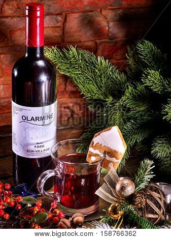 Bottle of red wine and mug with Christmas hot mulled wine. Label on bottle. Winter hot drink. Gingerbread cookie in form of house on mug. Christmas ball and Christmas tree.