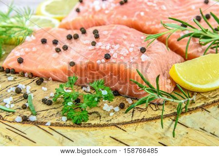 Fresh salmon steak on wooden birch stump pickled lemon pepper sea salt rosemary parsley dill