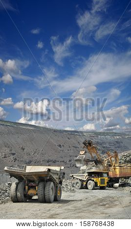 Heavy mining trucks are being loaded with iron ore on the opencast mining on a sunny day in summer