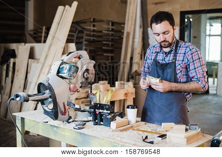 Cheerful carpentry worker having lunch eating sandwich in a workshop,