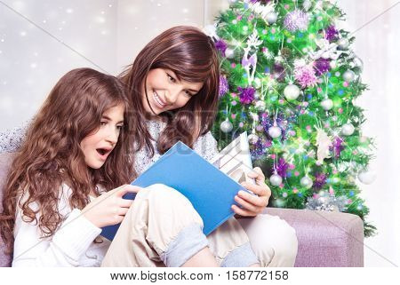 Happy family near Christmas tree, mother and daughter reading book on Christmas eve at home, enjoying interesting exciting fairy tale