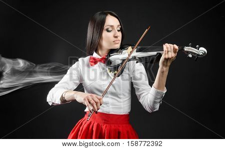 Attractive woman playing the violin on a black background and smoke