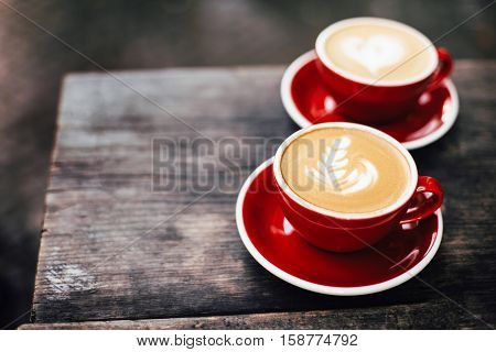 Two red cups of cappuccino with latte art on old wooden rustic table. Morning coffee for couple in love. Top view.