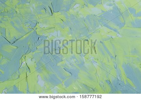 Abstract textured background: mixture of blue and green putty. Uneven strokes rough texture of a wall pattern