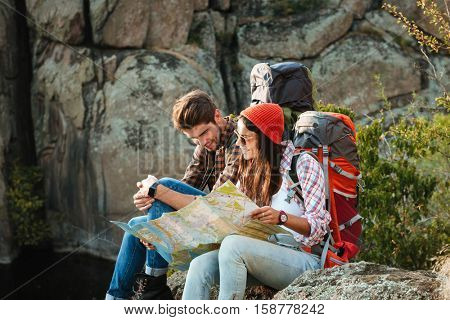 Young adventure couple with map sitting on slope. look at map