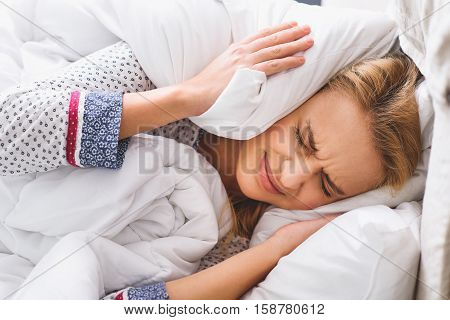 What a noise. Angry woman is covering her ears by pillow with frustration. She is lying in bed