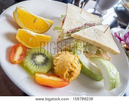 Closeup club sandwich breakfast made from ham tomato cheese and lettuce with orange guava and kiwi on white dish (Selective focus)
