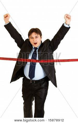 Pleased young businessman crossing finish line isolated on white. Concept - success achievement