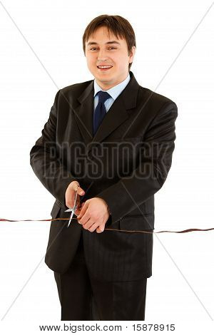 Smiling modern businessman cutting the red ribbon isolated on white. Concept - grand opening