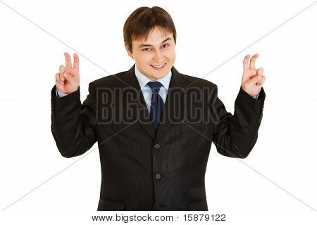 Smiling young businessman showing air quotes gesture isolated on white