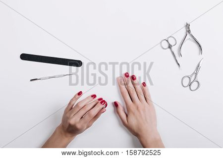 Women's Hands With A Red Manicure Scissors And Nail File On A White Table