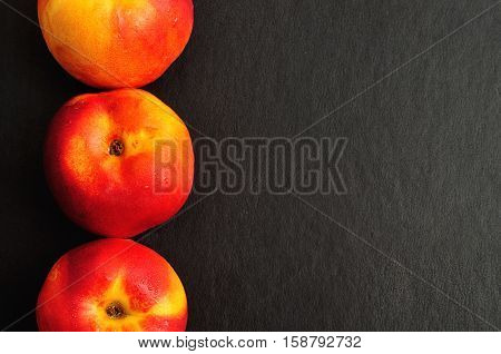 A row of Nectarines isolated on a black background