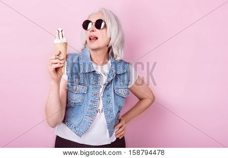 My passion. Emotional beautiful senior woman holding an icecrem and licking lips while standing against isolated pink background.