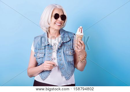 Happy moment. Pleasant senior cute woman smiling and holding an icecream while standing against isolated blue background.