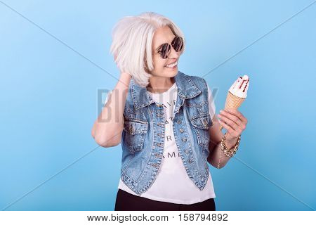 Want something sweet. Joyful senior pretty woman smiling and holding an icecream while standing against isolated blue background.