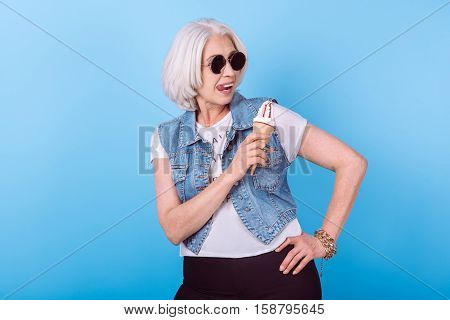 Funny lady. Emotional pretty senior woman licking lips and holding an icecream while standing against blue isolated background.