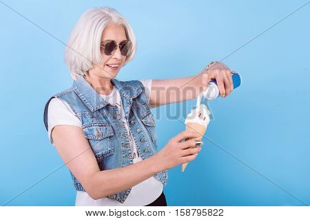 It will be tasty. Happy senior charming woman smiling and adding cream in icecream while standing against isolated blue background.