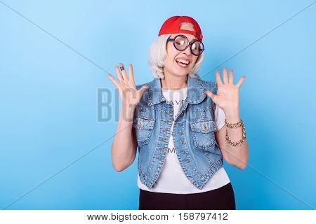 Be happy. Senior beautiful satisfied woman smiling and rising hands while standing against isolated blue background.