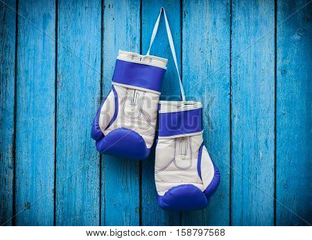 pair of blue boxing gloves hanging on a nail on a background of blue wooden surface