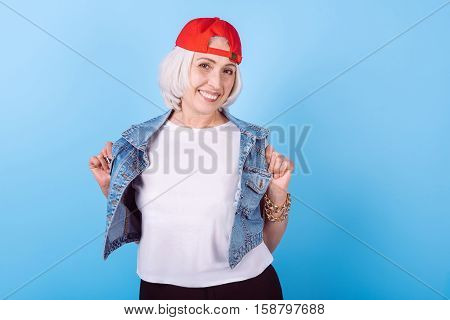 New style. Amused cute senior woman smiling and demonstration her vest while standing against isolated blue background.
