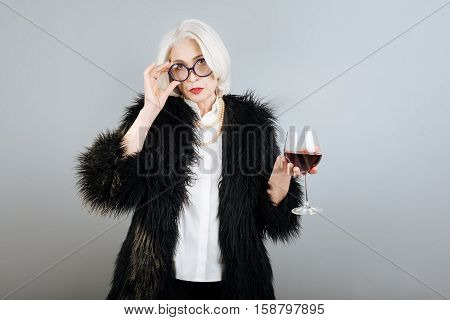 Favorite wine. Concentrated senior aristocratic woman holding wineglass and touching glasses while standing against isolated gray background.