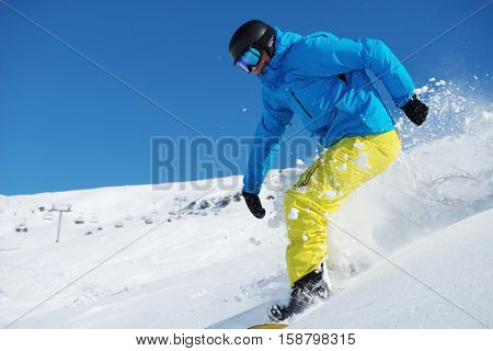 Snowboarder riding down the snowy hill in the ski resort