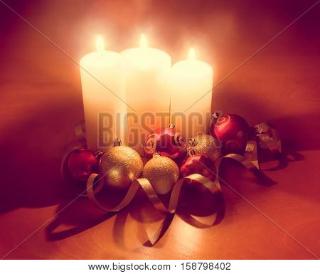 Burning candles with red and gold christmas balls
