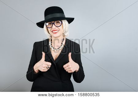 Perfect look. Charming senior pretty woman rising thumbs and smiling while standing against isolated gray background.