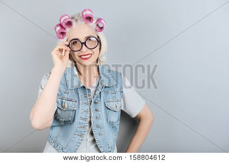 Ready for happiness. Senior pleasant pretty woman using headphones and smiling while standing against isolated gray background.