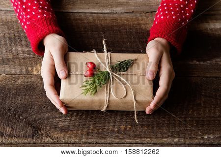 Hands of unrecognizable woman holding wrapped and decorated Christmas present against wooden table background. Studio shot. Close up