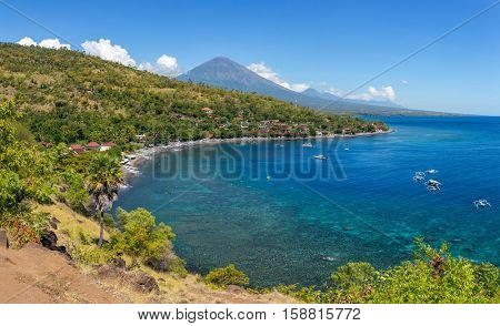 Jemeluk Beach and beautiful blue lagoon with Gunung Agung volcano on background. Amed village, East of Bali, Indonesia.