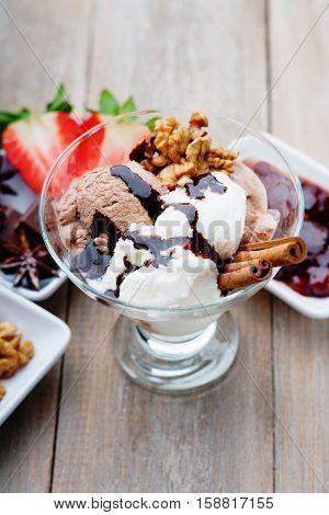 Ice cream sundae, chocolate, walnuts, sliced strawberry and jam on table