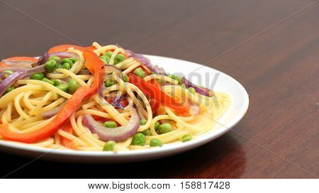 linguine pasta with vegetables in white plate on wooden table