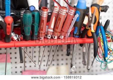 Important equipment. Close up of screwdrivers and pliers on the table in a workroom.