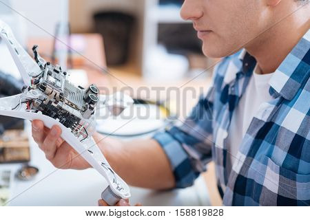 Hobby and job. Close up of handsome young concentrated man discovering drone detail while working as a repairman and sitting in his workroom.