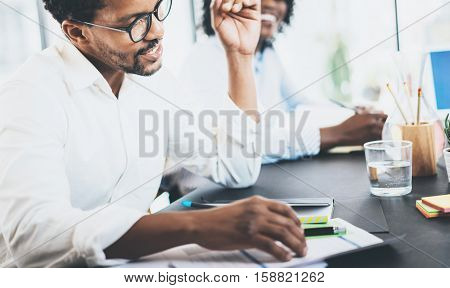 Black african coworker explaning business task in meeting room.Two young entrepreneurs working together in a modern office.Horizontal, blurred background