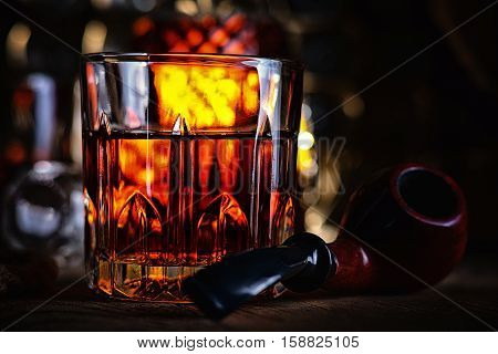 Glass of whiskey and tobacco pipe on a table