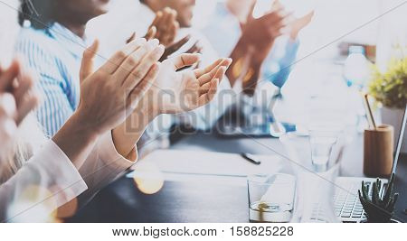 Close up of young business partners applauding to reporter after listening report at seminar. Professional education, work meeting, presentation or coaching concept.Horizontal, blurred background