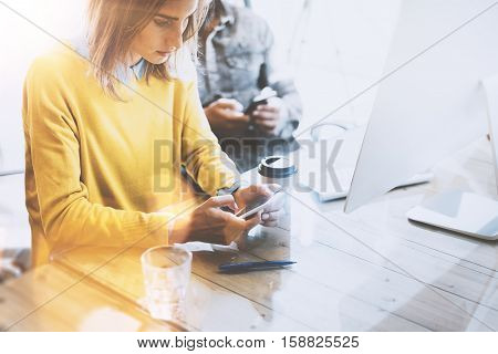 Young team of coworkers using together mobile devices in modern coworking space. Beautiful girl sending message with smartphone.Horizontal. Blurred background