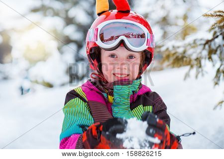 Young active skier in sport helmet playing with snow